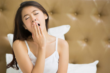 Asian women are yawning after she wake up.