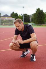 mann macht eine pause beim sport und schaut auf sein mobiltelefon
