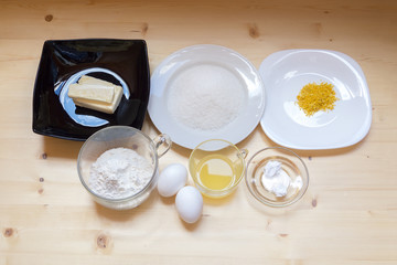 Ingredients for lemon muffins on a wooden surface