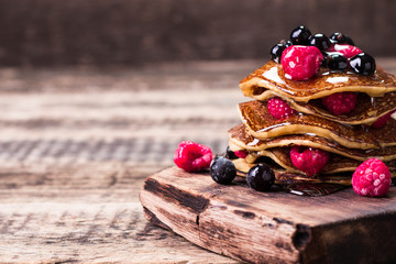 Buckwheat pancakes with berry fruit and honey on wooden vintage table