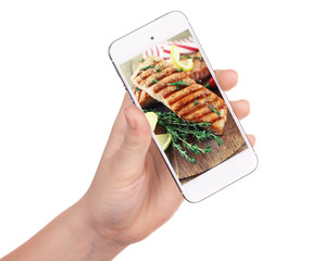 Female hand holding smartphone on white background. Photo of food on smartphone screen.