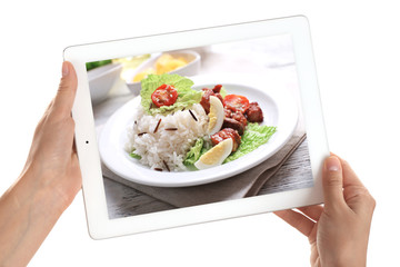 Female hands holding tablet on white background. Photo of food on tablet screen.