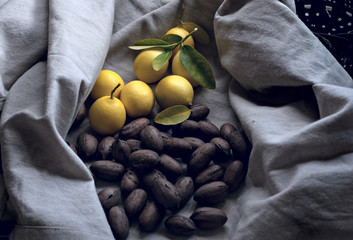 Autumn / winter still life. Lemons with green leaves and whole pecans on the cotton background. Dark photography