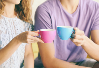 Couple  holding cups of coffee together