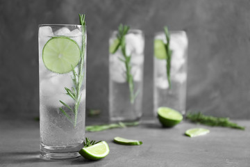 Glasses of cocktail with ice on grey background