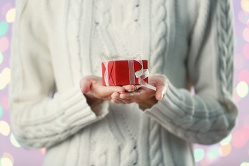 Woman holding Christmas gift box on color background