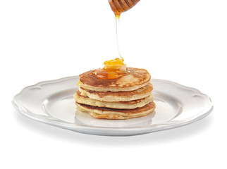 Tasty pancakes with honey and butter on plate, isolated on white