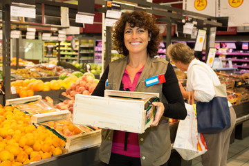 Cheerful female worker in supermarket holding a large wooden tray