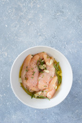 Raw chicken tenders marinated with garlic, olive oil, lemon juice, rosemary, thyme, salt and pepper in white bowl