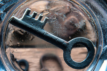 Old rusty key on the bottom of glass of water