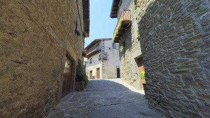 RUPIT CATALONIA SPAIN - JULY 2016: Smooth camera steady wide angle shot along narrow street in the old european spain village goes up, high colorful ancient walls with windows, clear sky with sun