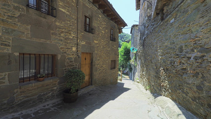 RUPIT CATALONIA SPAIN - JULY 2016: Smooth camera steady wide angle shot along narrow street in the old european spain village goes down, high colorful ancient walls with windows, clear sky with sun