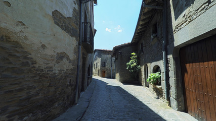 RUPIT CATALONIA SPAIN - JULY 2016: Smooth camera steady wide angle shot along narrow street in the old european spain village, high colorful ancient walls with windows, clear sky with sun