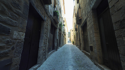 BESALU CATALONIA SPAIN - JULY 2016: Smooth camera steady wide angle shot along narrow street in the old european spain village goes up, high colorful ancient walls with windows, clear sky with sun