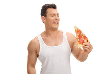Disgusted young guy looking at a slice of pizza