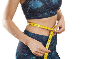 Young woman with tape measure around waist