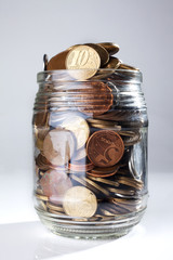 A jar full of Brazilian coins isolated on white background
