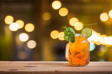 Fresh cocktail with lemon tea on wooden counter bar over blurred photo of restaurant background