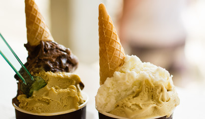 Italian ice cream cups with waffle cones on top of it. Dessert for couple of travelers.