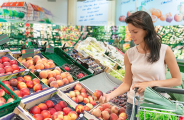woman selecting fruit in a grocery store