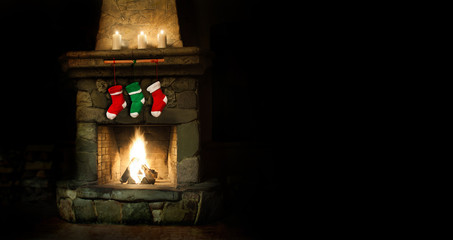 Romantic merry christmas postcard template. Colorful stockings on fireplace collage. green red socks for gifts. Xmas interior with chimney place, candles. Copy space, copytext black background.