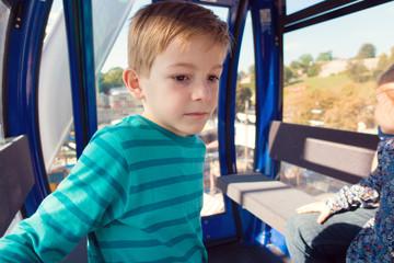 Cute little boy sitting in ferris wheel cabin at oktoberfest