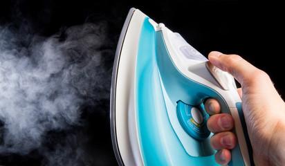 Modern iron in hand blowing off steam