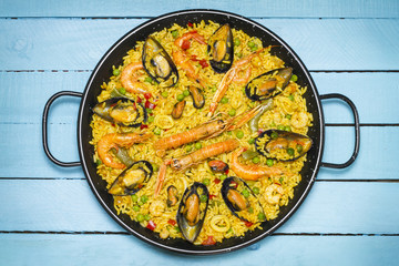 Spanish paella on a wooden table.