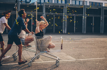 Friends racing with shopping cart Wall mural