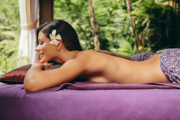Young woman lying on massage table in tropical resort