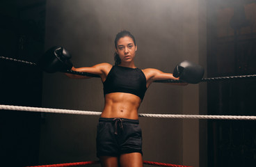 Portrait of female boxer leaning against ropes of boxing ring