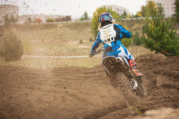 Moto cross - MX girl biker at race in Russia - a sharp turn and the spray of dirt, rear view