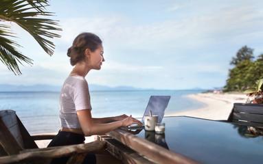 women use laptop in cafe office near sand beach