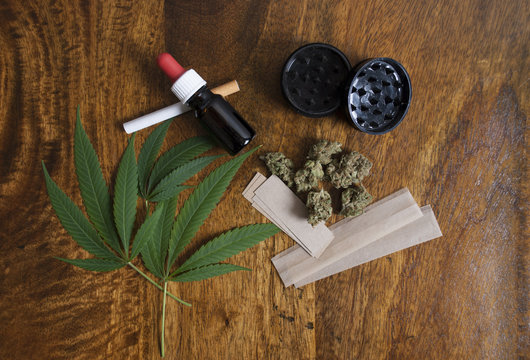 Cannabis sativa leafs and THC oil, with grinder and papers to smoke weed joint on wooden background