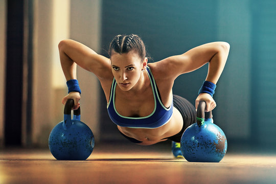 Young fit woman is training by kettlebell.