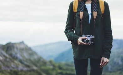 Hipster girl with backpack enjoying sunset on peak of foggy mountain, tourist traveler taking pictures of amazing landscape on vintage photo digital camera on background valley view mockup sun flare