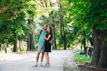 Friends or couple of lovers making selfie photo on motion camera in park of Europe