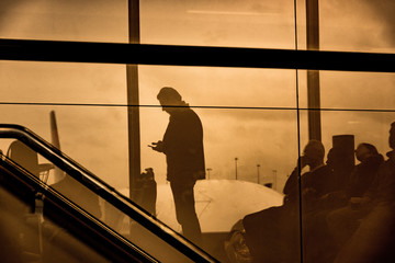 Man looking at phone in Schiphol airport in Amsterdam, Netherlands