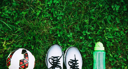 Sports shoes sneakers, ball and bottle of water on a fresh green grass