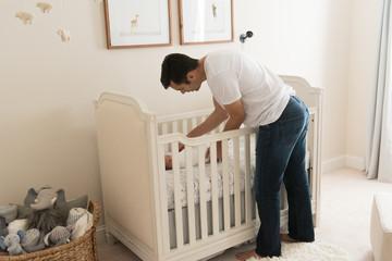 HIspanic dad putting newborn baby in crib