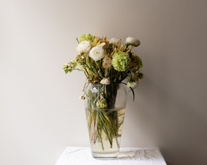 Wilting green and white ranunculus and carnations in large glass vase on small white table