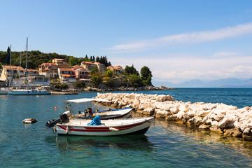 Traditional fishing boats and emerald sea water in Kassiopi port. Corfu Island. Greece.