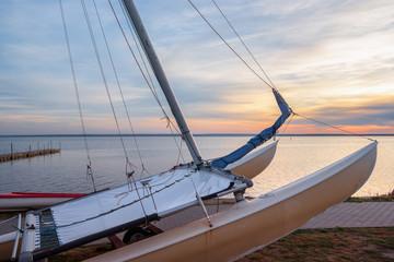 Closeup of a catamaran on a seashore at sunset.