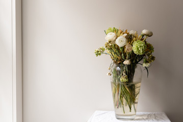 Wilting green and white ranunculus and carnations in large glass vase on small white table next to window