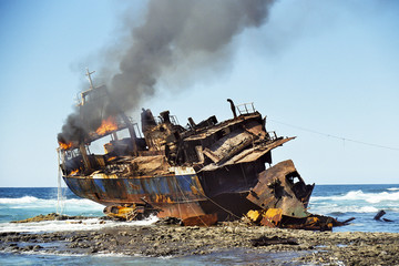 Stranded fish cutter lying burning at a reef.