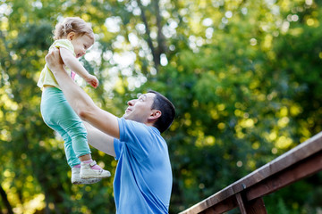 Dad holds baby daughter in his arms high in park