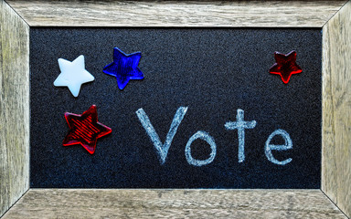 Vote written on chalkboard, surrounded by red, white and blue stars.  National event of voting for government official.  Election symbols.