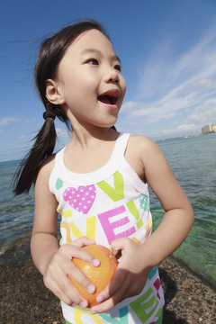 A young girl holds an orange and poses for the camera at the water's edge;Honolulu oahu hawaii united states of america