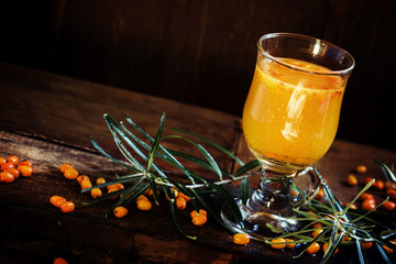 Sea buckthorn lemonade, dark wood background, selective focus