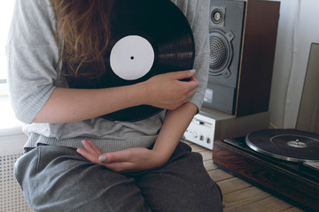girl with long hair keep the vinyl disk on hands.